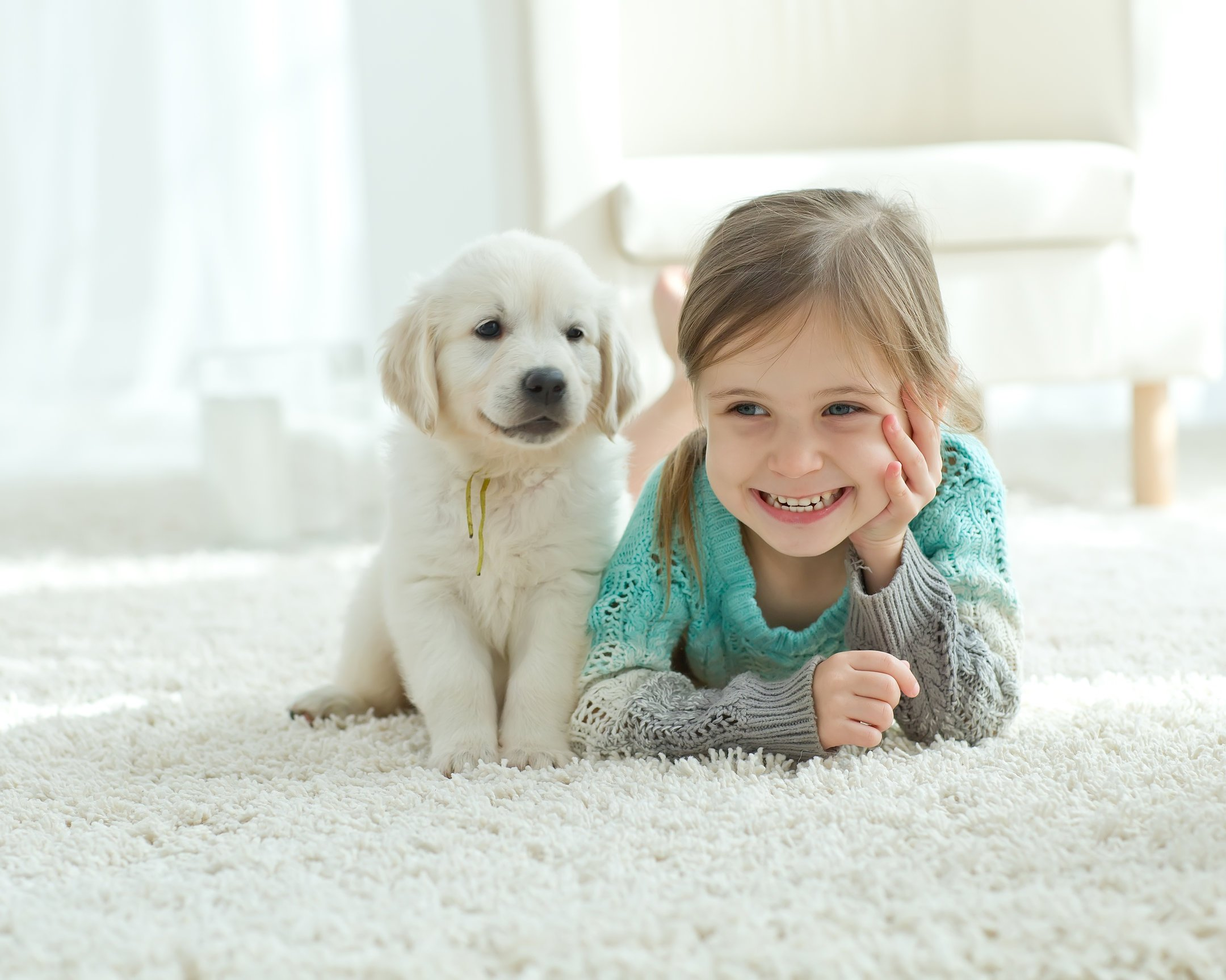 Girl and puppy laying on white carpet
