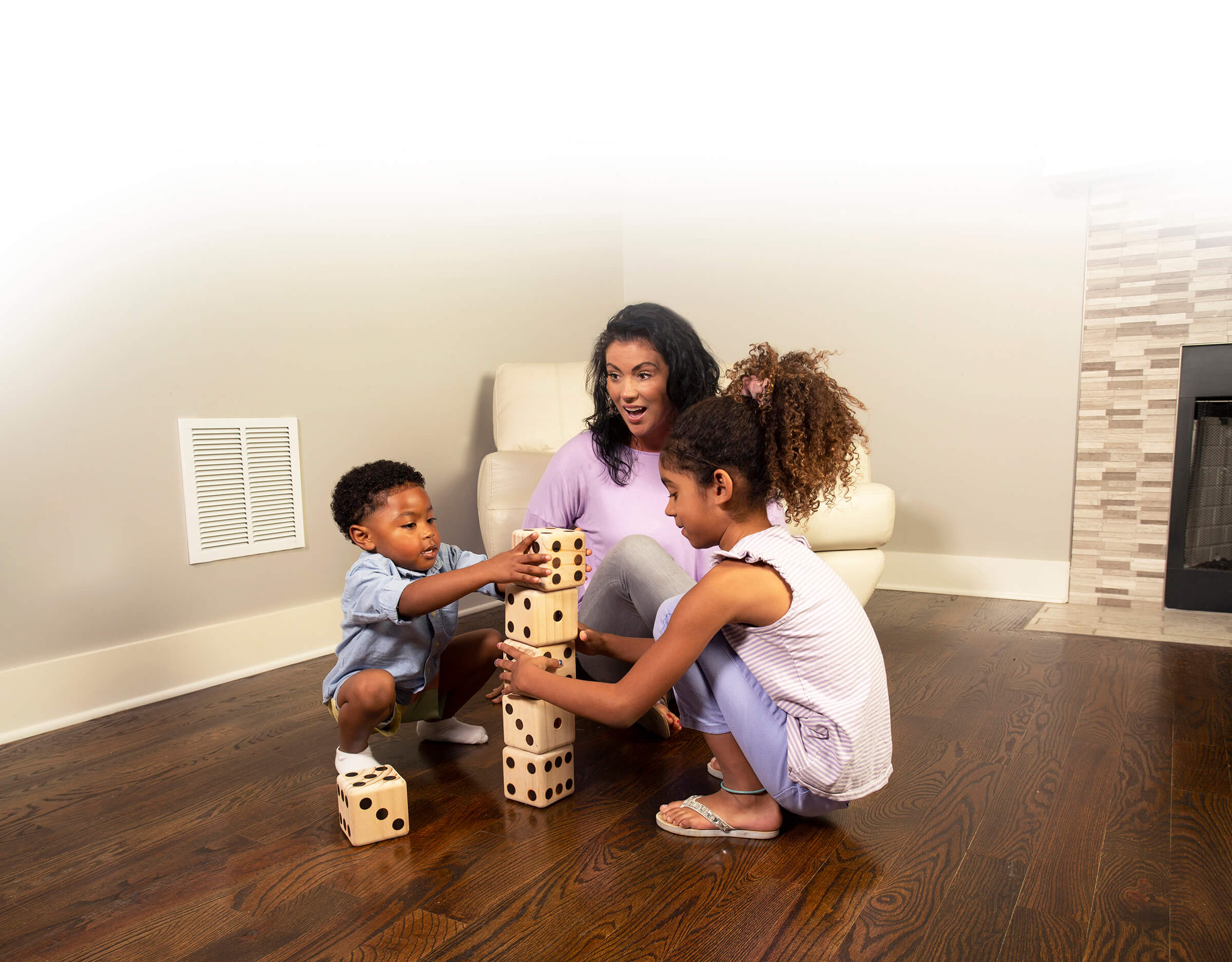 Mom and children playing on wood floors in Long Beach